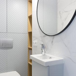 Свежая идея для дизайна: туалет в скандинавском стиле с плоскими фасадами, серыми фасадами, раздельным унитазом, белой плиткой, накладной раковиной и белым полом - отличное фото интерьера
