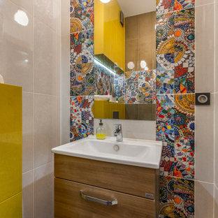 На фото: туалет в современном стиле с плоскими фасадами, фасадами цвета дерева среднего тона, разноцветной плиткой, консольной раковиной и синим полом
