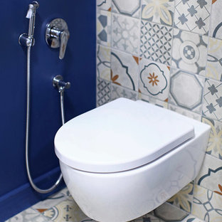 Design ideas for a medium sized contemporary cloakroom in Saint Petersburg with a wall mounted toilet, porcelain tiles, blue walls, porcelain flooring, multi-coloured floors and multi-coloured tiles.