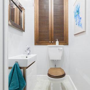 Стильный дизайн: туалет в современном стиле с плоскими фасадами, белыми фасадами, раздельным унитазом, белыми стенами, белым полом и накладной раковиной - последний тренд