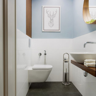 Пример оригинального дизайна: маленький туалет в скандинавском стиле с плоскими фасадами, коричневыми фасадами, инсталляцией, белой плиткой, керамогранитной плиткой, накладной раковиной, столешницей из дерева, серым полом и коричневой столешницей