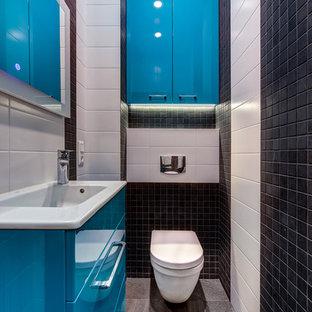 Новый формат декора квартиры: туалет в современном стиле с плоскими фасадами, синими фасадами, инсталляцией, белой плиткой, черной плиткой, монолитной раковиной и серым полом
