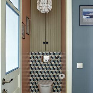 На фото: туалеты в стиле современная классика с инсталляцией, плоскими фасадами и синей плиткой