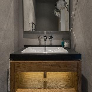 Свежая идея для дизайна: туалет в современном стиле с плоскими фасадами, фасадами цвета дерева среднего тона, серой плиткой, накладной раковиной и черной столешницей - отличное фото интерьера