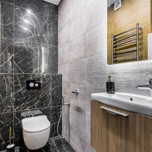 Свежая идея для дизайна: туалет среднего размера в современном стиле с плоскими фасадами, светлыми деревянными фасадами, инсталляцией, керамогранитной плиткой, полом из керамогранита, монолитной раковиной, черным полом, белой столешницей, черной плиткой и подвесной тумбой - отличное фото интерьера