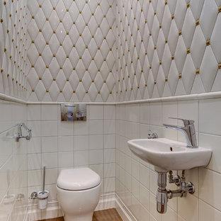 Пример оригинального дизайна: туалет в современном стиле с инсталляцией, белой плиткой, подвесной раковиной и коричневым полом