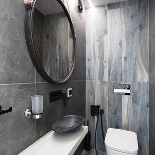 На фото: туалет в современном стиле с инсталляцией, серой плиткой, настольной раковиной и серым полом с