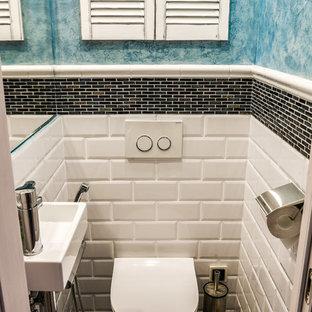 Esempio di un piccolo bagno di servizio contemporaneo con WC sospeso, pareti blu, pavimento in terracotta, lavabo integrato e pavimento grigio