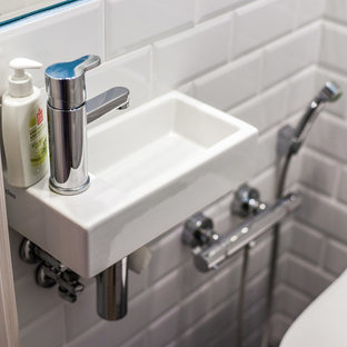 Immagine di un piccolo bagno di servizio contemporaneo con WC sospeso, pareti blu, pavimento in terracotta, lavabo integrato e pavimento grigio