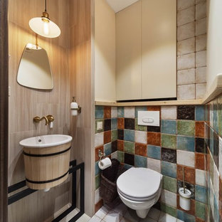 Photo of a contemporary cloakroom in Yekaterinburg with a wall mounted toilet, beige tiles, multi-coloured tiles, a console sink and white floors.