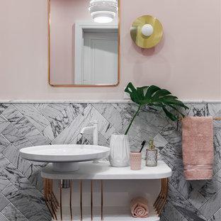 На фото: туалет в современном стиле с открытыми фасадами, серой плиткой, мраморной плиткой, розовыми стенами и настольной раковиной
