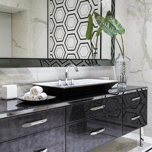 Свежая идея для дизайна: туалет в современном стиле с плоскими фасадами, черными фасадами, бежевыми стенами, настольной раковиной, стеклянной столешницей и бежевым полом - отличное фото интерьера