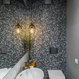 Пример оригинального дизайна интерьера: туалет в современном стиле с инсталляцией, серой плиткой, серыми стенами, настольной раковиной, столешницей из дерева, коричневым полом и коричневой столешницей