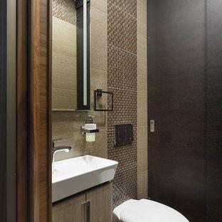 Idées déco pour des WC et toilettes contemporains de taille moyenne avec un WC suspendu, un carrelage marron, des carreaux de céramique, un mur marron, un sol en carrelage de céramique, un placard à porte plane, des portes de placard en bois clair et une vasque.