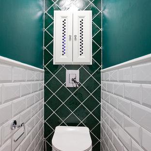 Cette image montre un WC et toilettes traditionnel avec un WC suspendu, un carrelage blanc, un carrelage métro et un mur vert.