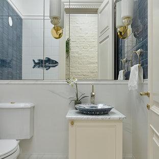 На фото: туалеты в классическом стиле с бежевыми фасадами, синей плиткой, белой плиткой, керамогранитной плиткой, полом из керамогранита, мраморной столешницей, фасадами с утопленной филенкой, раздельным унитазом, белыми стенами, настольной раковиной и белым полом
