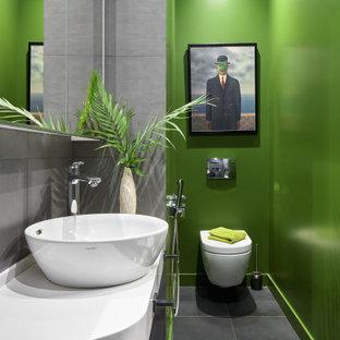 Пример оригинального дизайна: туалет в современном стиле с инсталляцией, серой плиткой, зелеными стенами, настольной раковиной, серым полом и белой столешницей
