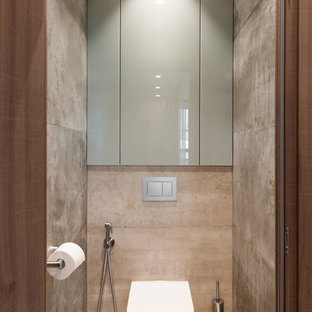 Photo of a medium sized contemporary cloakroom in Saint Petersburg with glass-front cabinets, a wall mounted toilet, beige tiles, porcelain tiles, beige walls, porcelain flooring and beige floors.