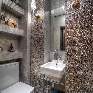 На фото: маленький туалет в современном стиле с полом из керамической плитки, подвесной раковиной, раздельным унитазом и металлической плиткой с