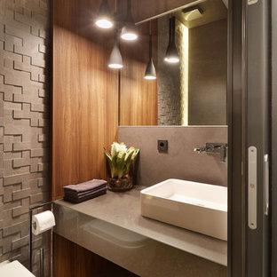 Создайте стильный интерьер: туалет среднего размера в современном стиле с настольной раковиной, столешницей из искусственного кварца, инсталляцией, коричневыми стенами, коричневым полом и коричневой столешницей - последний тренд