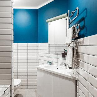 Новые идеи обустройства дома: туалет в современном стиле с плоскими фасадами, белыми фасадами, белой плиткой, плиткой кабанчик, синими стенами, врезной раковиной и серым полом