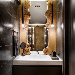 На фото: туалеты в современном стиле с плоскими фасадами, черными фасадами, черной плиткой, паркетным полом среднего тона, монолитной раковиной, коричневым полом и белой столешницей