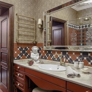 Стильный дизайн: маленький туалет с фасадами с выступающей филенкой, коричневыми фасадами, раздельным унитазом, коричневой плиткой, керамической плиткой, коричневыми стенами, полом из керамической плитки, накладной раковиной, мраморной столешницей, разноцветным полом и бежевой столешницей - последний тренд