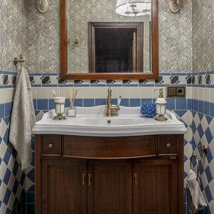 На фото: маленький туалет с фасадами островного типа, темными деревянными фасадами, бежевой плиткой, синей плиткой, серыми стенами, монолитной раковиной, синим полом и белой столешницей