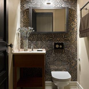 На фото: туалеты в современном стиле с инсталляцией, разноцветной плиткой, бежевыми стенами, врезной раковиной, белым полом, плоскими фасадами, фасадами цвета дерева среднего тона и белой столешницей