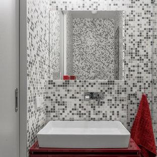 Immagine di un piccolo bagno di servizio design con ante lisce, ante rosse, WC sospeso, piastrelle grigie, piastrelle a mosaico, pareti grigie, pavimento in cementine, lavabo a bacinella, top in laminato, pavimento grigio e top rosso