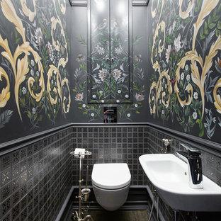 Foto de aseo bohemio con sanitario de pared, baldosas y/o azulejos negros, paredes negras, suelo marrón y lavabo suspendido