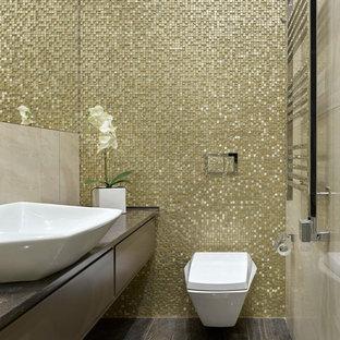 Imagen de aseo actual con armarios con paneles lisos, sanitario de pared, baldosas y/o azulejos en mosaico, lavabo sobreencimera, suelo marrón, puertas de armario marrones y encimeras marrones