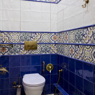 Photo of a mediterranean cloakroom in Moscow with a wall mounted toilet, blue tiles, white tiles and multi-coloured tiles.