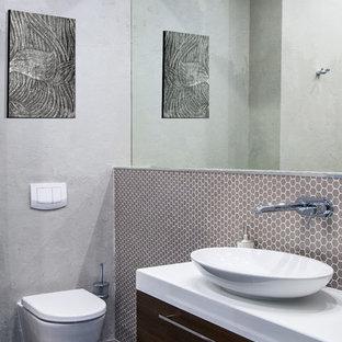 Удачное сочетание для дизайна помещения: туалет в современном стиле с плоскими фасадами, фасадами цвета темного дерева, настенным унитазом, серой плиткой, плиткой мозаикой, серыми стенами, настольной раковиной, черным полом и белой столешницей - самое интересное для вас