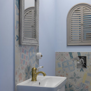 This is an example of a classic cloakroom in Moscow with flat-panel cabinets, white cabinets, multi-coloured tiles, a wall mounted toilet, an integrated sink and blue walls.