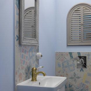 На фото: туалет в классическом стиле с плоскими фасадами, белыми фасадами, разноцветной плиткой, инсталляцией, монолитной раковиной и синими стенами