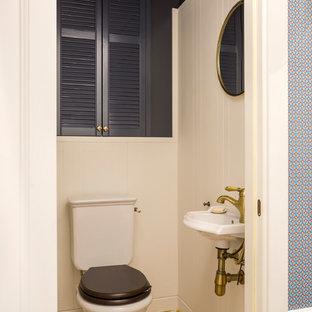 На фото: туалет в современном стиле с раздельным унитазом, синими стенами, подвесной раковиной и разноцветным полом с