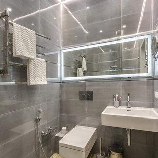 На фото: туалет в современном стиле с настенным унитазом, серой плиткой, подвесной раковиной и бежевым полом с