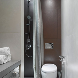 Modelo de aseo actual con sanitario de pared, baldosas y/o azulejos marrones, baldosas y/o azulejos de porcelana, suelo de baldosas de porcelana y paredes multicolor