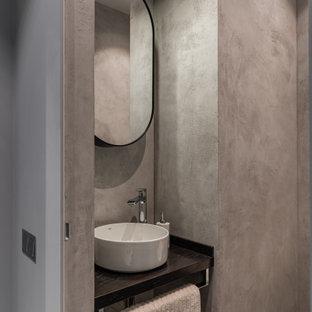 На фото: туалет среднего размера в современном стиле с открытыми фасадами, серой плиткой, полом из мозаичной плитки, настольной раковиной, серым полом и черной столешницей с