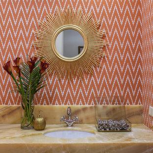 Идея дизайна: туалет в стиле современная классика с оранжевыми стенами, врезной раковиной и столешницей из оникса