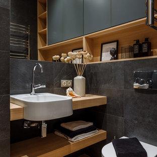 Foto de aseo actual con sanitario de una pieza, baldosas y/o azulejos negros, lavabo encastrado, encimera de madera, suelo marrón, encimeras marrones y armarios abiertos