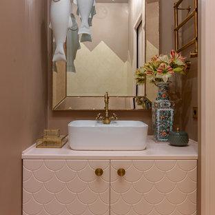 Неиссякаемый источник вдохновения для домашнего уюта: туалет в современном стиле с бежевыми стенами, настольной раковиной, разноцветным полом, плоскими фасадами и розовой столешницей