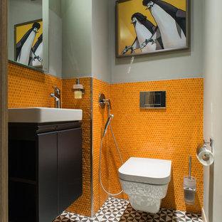 Cette photo montre un petit WC et toilettes tendance avec un placard à porte plane, des portes de placard noires, un WC suspendu, un carrelage orange, un carrelage noir et blanc, carrelage en mosaïque, un mur gris, un lavabo intégré et un sol multicolore.