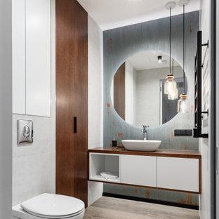 Пример оригинального дизайна: туалет в современном стиле с плоскими фасадами, белыми фасадами, инсталляцией, настольной раковиной, коричневым полом, коричневой столешницей и подвесной тумбой