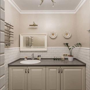 На фото: туалеты в классическом стиле с фасадами с выступающей филенкой, бежевыми фасадами, белой плиткой, коричневой плиткой, бежевыми стенами, накладной раковиной, разноцветным полом и серой столешницей