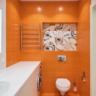 На фото: туалет среднего размера в стиле лофт с плоскими фасадами, белыми фасадами, инсталляцией, оранжевой плиткой, керамической плиткой, оранжевыми стенами, полом из керамической плитки, врезной раковиной, столешницей из искусственного камня, белым полом и белой столешницей с