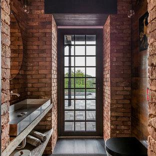 На фото: туалеты в стиле лофт с инсталляцией, настольной раковиной, столешницей из дерева, черным полом, открытыми фасадами, светлыми деревянными фасадами, красными стенами и бежевой столешницей