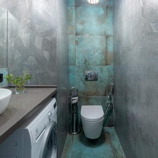 Ejemplo de aseo actual con sanitario de pared, baldosas y/o azulejos azules, paredes grises, lavabo sobreencimera, suelo azul y encimeras grises