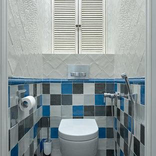 На фото: туалет в современном стиле с инсталляцией, синей плиткой, белой плиткой, серой плиткой и серым полом с